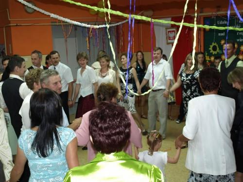 """Uczniowie, rodzice oraz nauczyciele podczas tańca do piosenki """"Cudownych rodziców mam""""."""