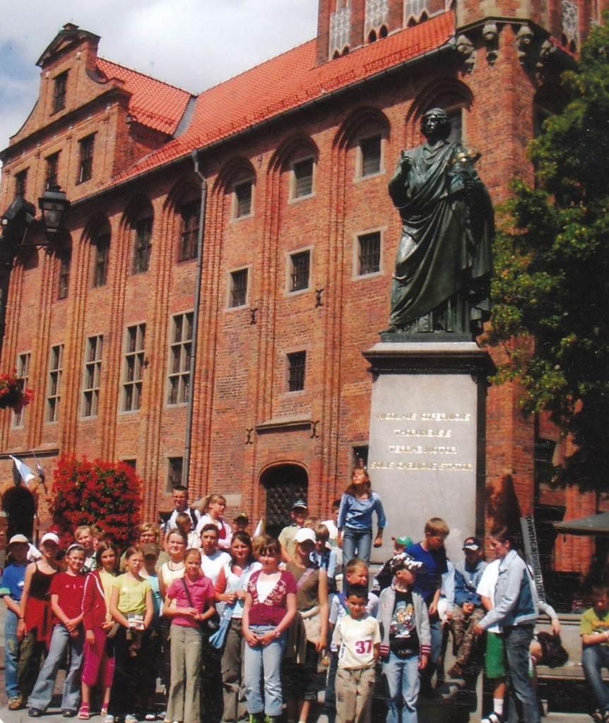 Uczniowie oraz opiekunowie przed Pomnikiem Mikołaja Kopernika w Toruniu.