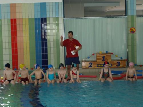 Dzieci podczas nauki pływania wraz instruktorem – trenerem nauki pływania.